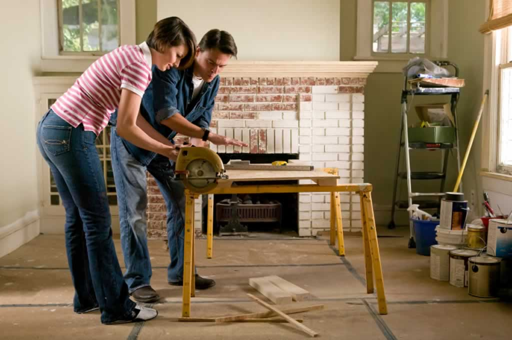 Tips to remember when undergoing a DIY home renovation project - couple sawing