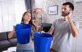 What to do When Water is Leaking from the Ceiling - holding buckets
